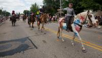 A youngster throws candy to the crowd from his horse during the Fourth of July parade in Pittsville