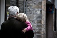 A man with white hair carries a sleeping child