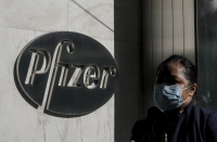 A person walks past a building with a Pfizer sign