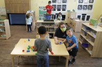 Caregivers at a daycare wear masks while kids play
