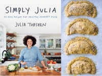 Julia stands behind her kitchen counter ready to cook on the cover of her new cookbook.