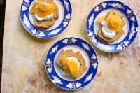 Three small ornamental blue plates with pieces of cake topped with oranges and yogurt.