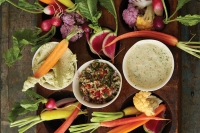 A spread of vegetables and various dips, including Kale Stem Hummus