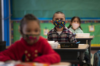 Kindergarten students wearing face masks sit in their classroom
