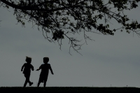 Kids running near a tree.