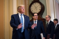 Treasury Secretary Steven Mnuchin listens and President Donald Trump arrives to speak with reporters