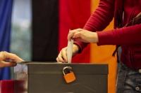 A person entering a ballot into a ballot box