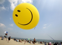 Smiley face balloon on the beach