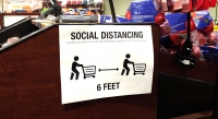 A store sign recommends social distancing