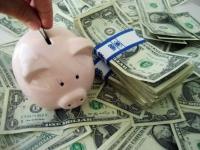 A hand puts a coin into a piggy bank