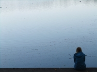 Woman sitting alone near the water