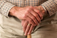 Elderly hands on cane