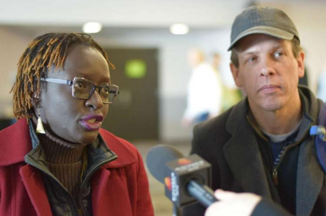 Photo of a black woman speaking earnestly into a WPR microphone while white man looks on