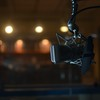 a studio microphone on a boom stand floating in front of lights