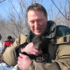 imae of Glen Moberg in winter holding a bear cub