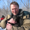 Photo of Glen Moberg holding bear cub
