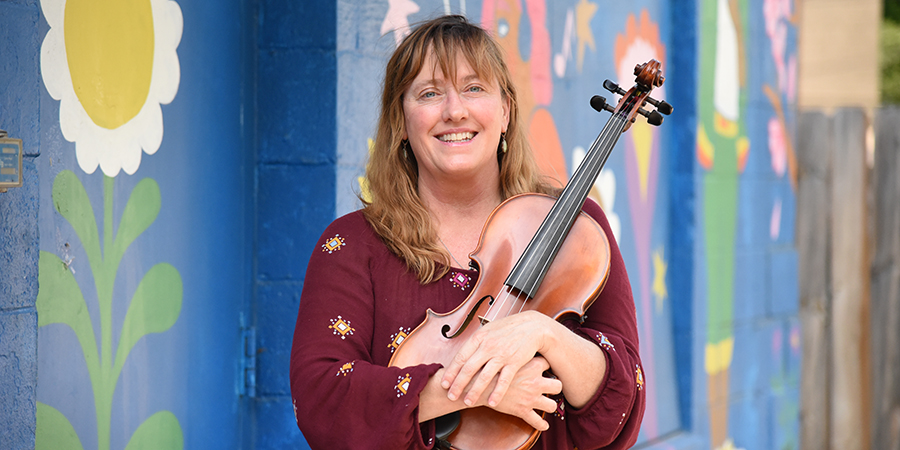 Sile Shigley holds a fiddle standing in front of a colorful mural wall